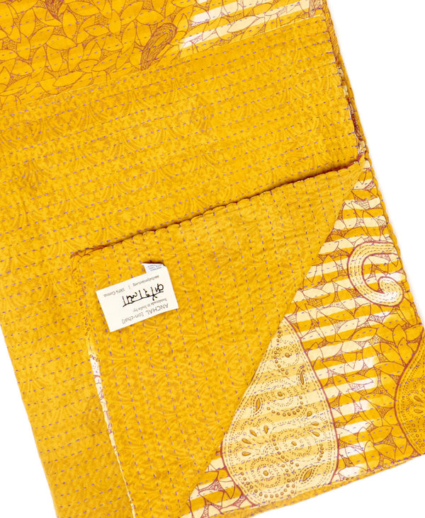 Fair trade orange kantha throw quilt handstitched by Anchal artisans in Ajmer India with large paisley and striped designs