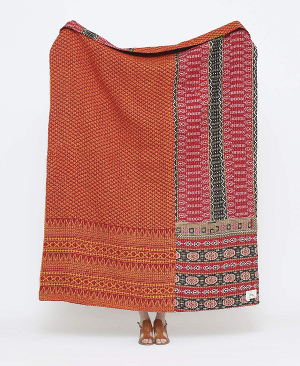 Orange and red vintage throw quilt with black detailing and small paisley and striped designs with white kantha stitching