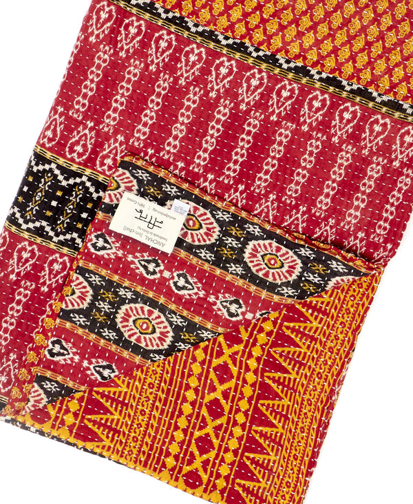 Fair trade orange and red kantha throw quilt handstitched by Anchal artisans in Ajmer India with tiny paisley and striped designs