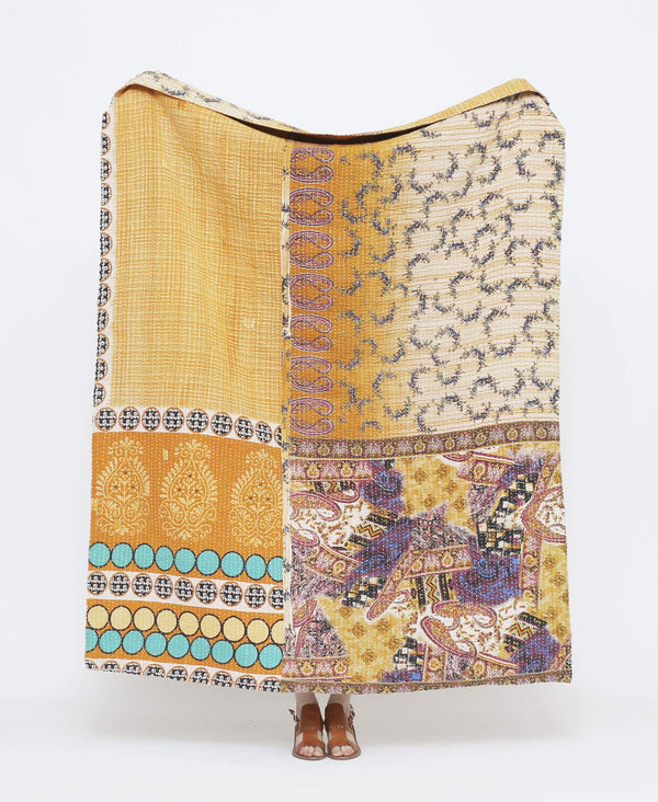 Orange and purple vintage throw quilt with white and teal blue detailing and a mod podge of paisley designs with white kantha stitching