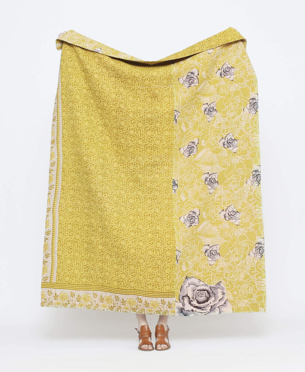 Yellow vintage throw quilt with white and black detailing and large rose floral prints with purple kantha stitching