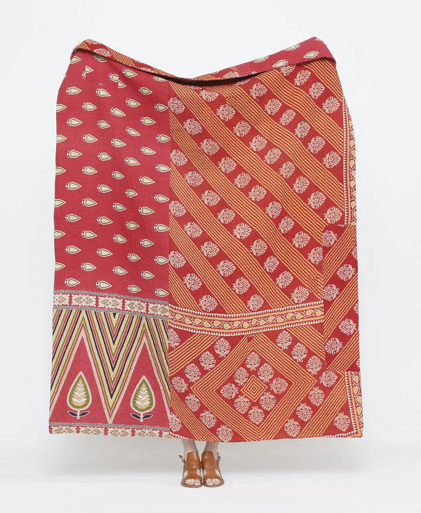 Red and orange vintage throw quilt with white and green detailing and striped geometric shapes and leaf prints with purple kantha stitching