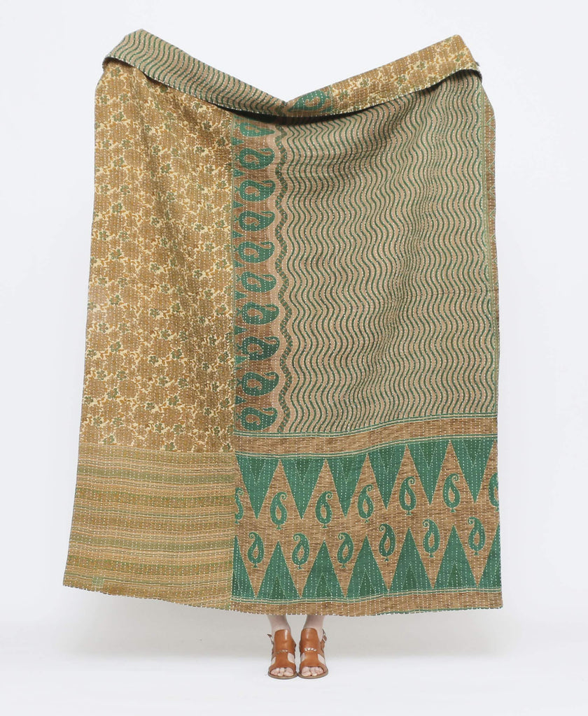 Green and brown vintage throw quilt with yellow detailing and floral, paisley, and wavy striped prints with white kantha stitching