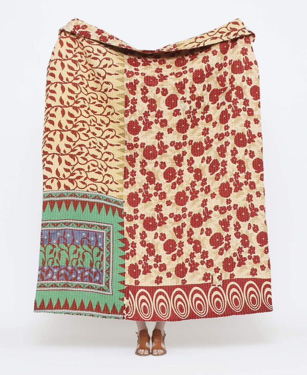 Red and beige vintage throw quilt with green and blue detailing and floral, and circular and triangle geometric prints with white kantha stitching