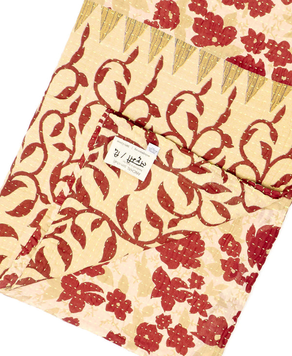 Fair trade red and beige throw quilt handstitched by Anchal artisans in Ajmer India with floral and geometric designs