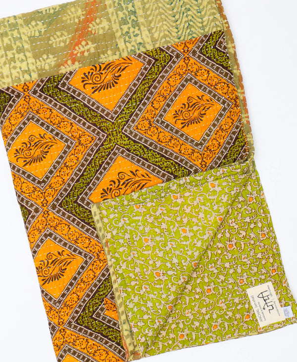 this one-of-a-kind green and orange quilt features a unique name tag of the individual artisan that created the blanket