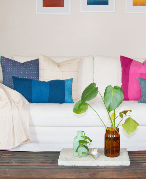 bright colorful throw pillows on all white sofa by Anchal