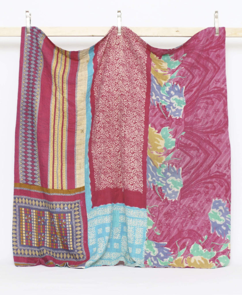 Quilt bedding using traditional kantha techniques to blend various vintage saris in colors of magenta, light blue, and yellow