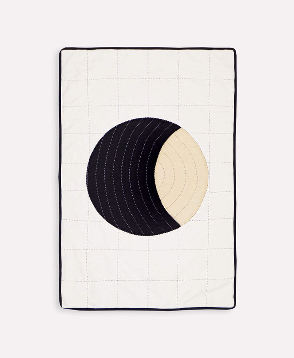 Small throw quilt featuring lunar hand-stitched pattern made with organic cotton