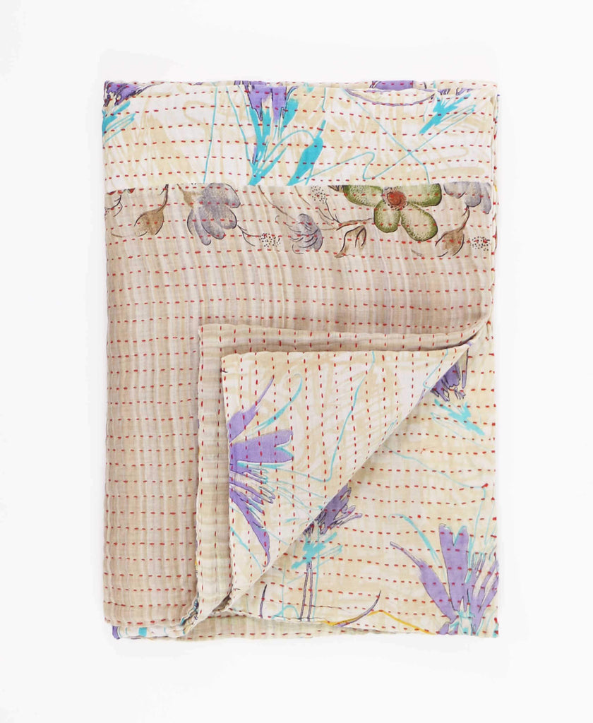 tan small quilt with blue and purple flowers