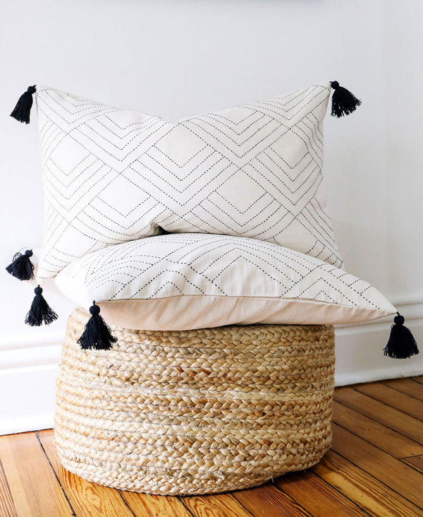 embroidered organic throw pillow with tassels on woven pouf