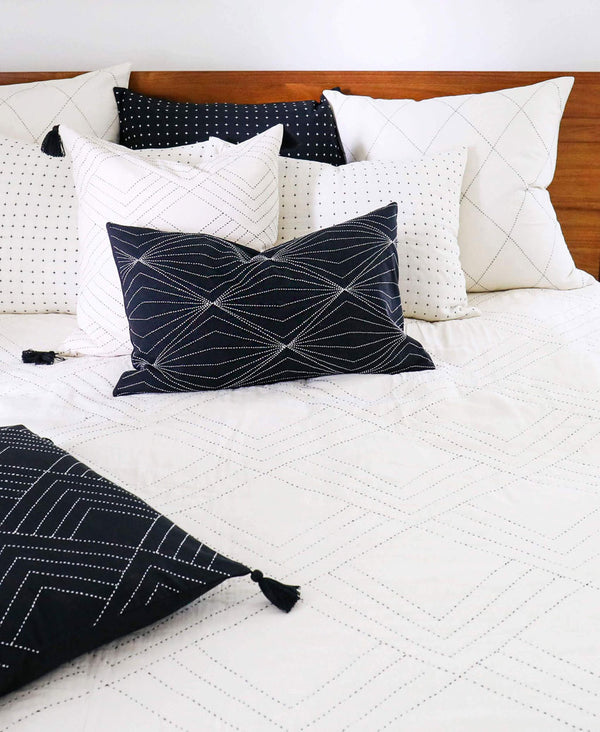 Bedding styled with bone colored geometric quilt and various pillows of different patterns