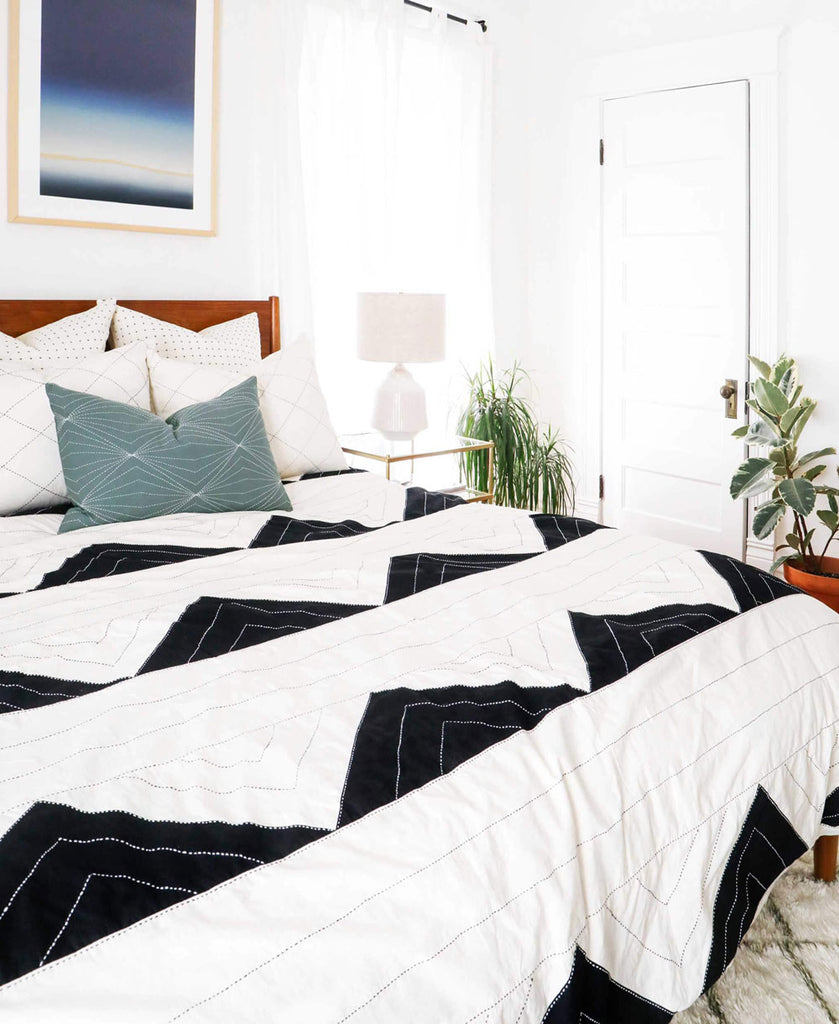 Bone and charcoal geometric bedding styled in a bedroom with coordinated pillow arrangement