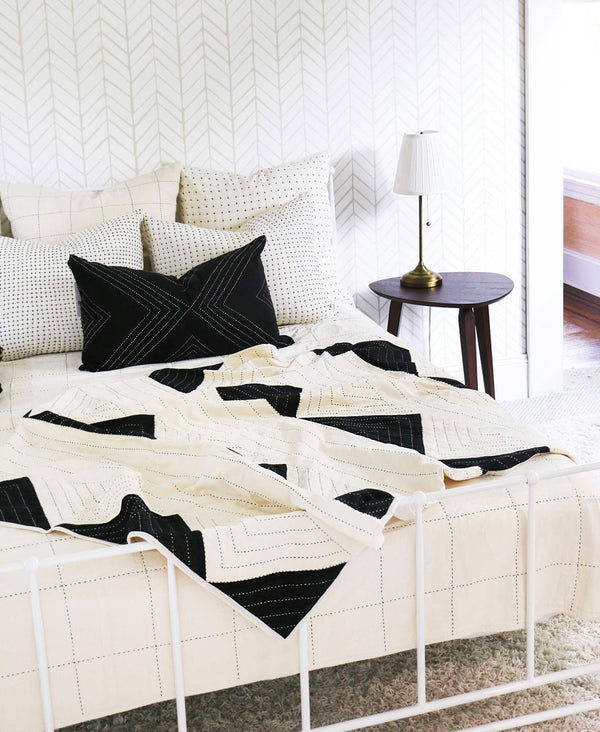 Triangle quilt throw styled in modern minimalist bedroom that pairs perfectly with Anchal Project pillows and throws
