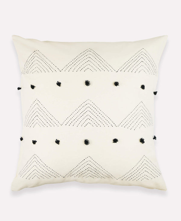 Embroidered triangle throw pillow with black pom poms