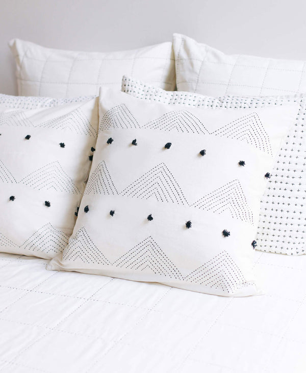 Embroidered triangle throw pillows featuring tassel details styled on minimalist bedding