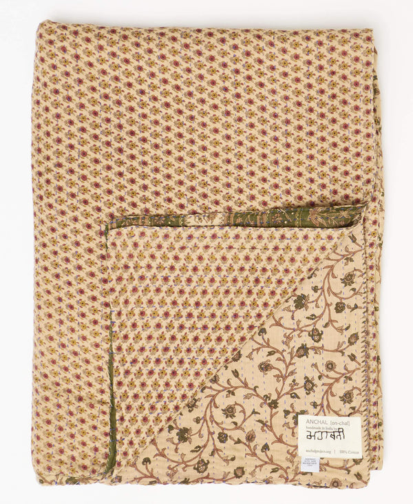 Tan and green twin kantha quilt with petite yellow and red floral patterns and blue stitching