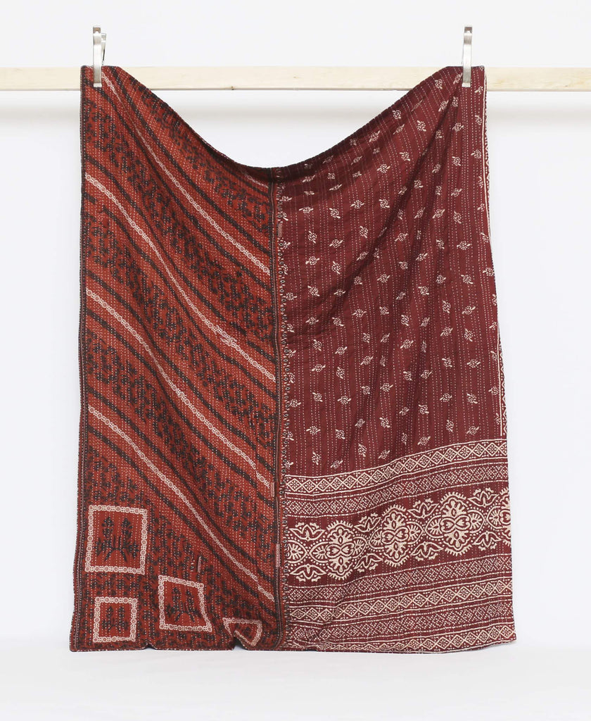 Maroon twin quilt with black and white floral and striped patterns and white kantha stitching