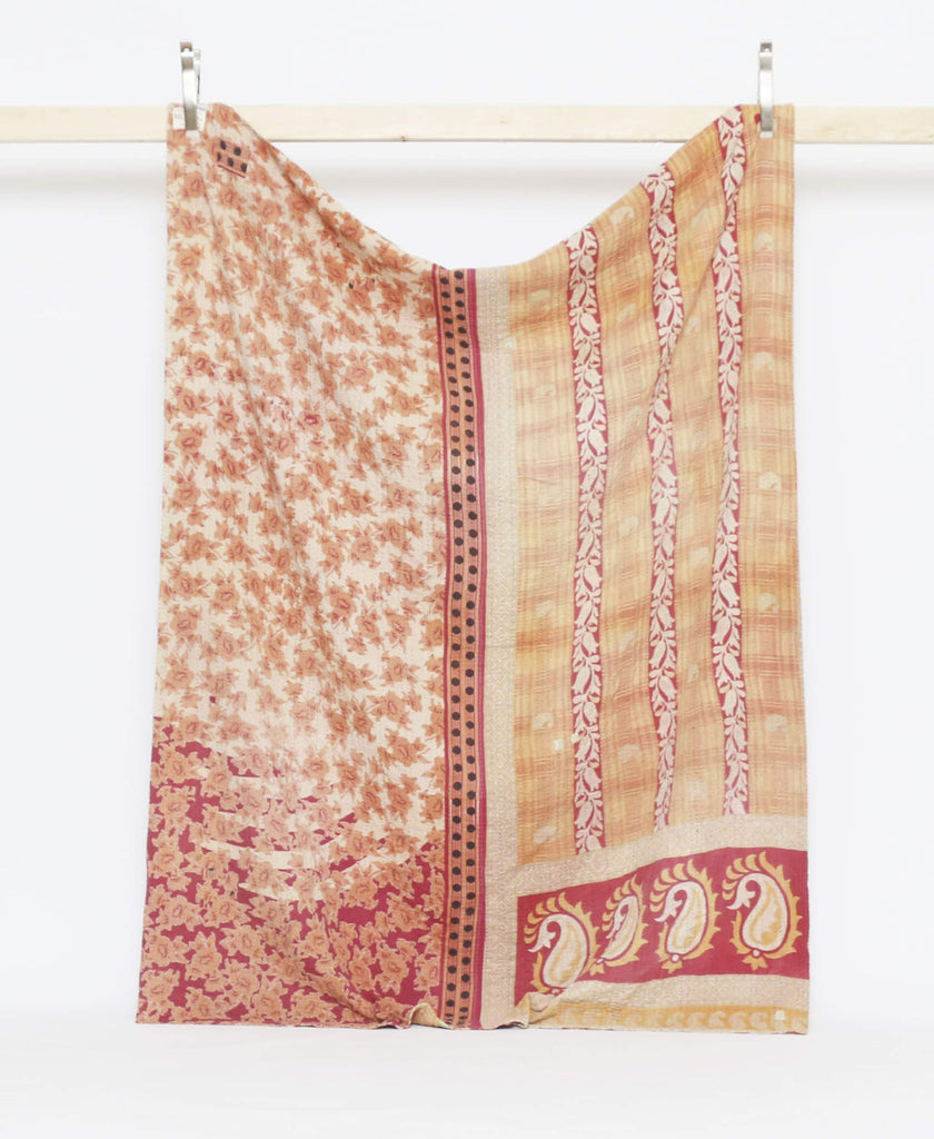 Orange and red twin quilt with bold floral and paisley prints and purple knatha stitching