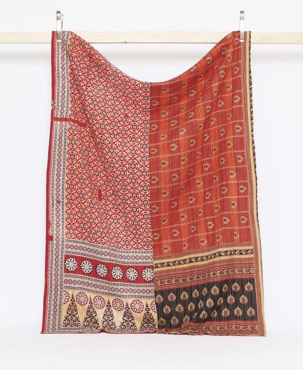 Orange and red vintage kantha twin quilt with floral designs and wite kantha stitching