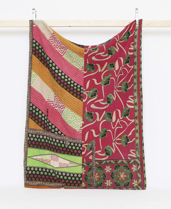 Dark pink and green vintage twin quilt with yellow and bright green floral patters and black kantha stitching