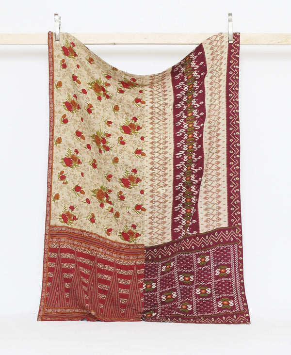 Tan and maroon vintage twin quilt with a bright red rose with purple kantha stitching