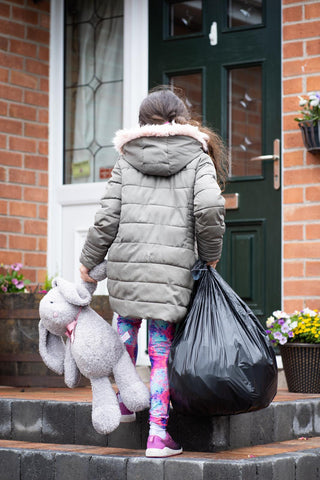 Child in care with their belongings in a bin bag