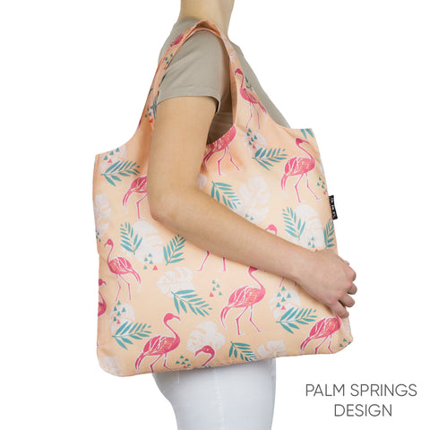 Envirosax reusable grocery bag with a pattern of pink flamingos and palm leaves on a light pink background