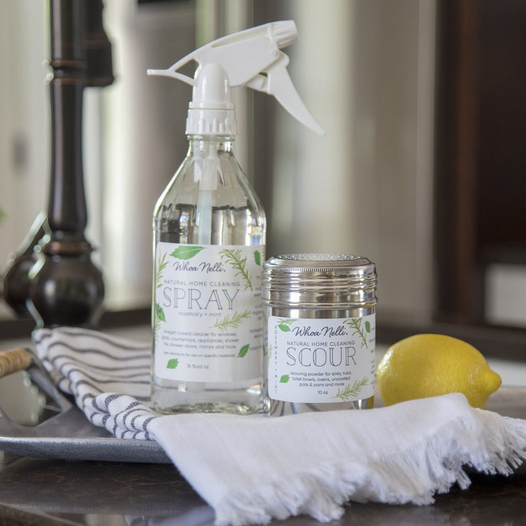 A glass spray bottle of natural vinegar cleaner and a stainless steel canister of powdered cleaners on a tray with a hand towel next to a kitchen faucet