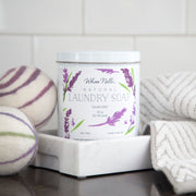 Two purple and green wool dryer balls placed next to a canister of Whoa Nelli lavender laundry soap and a rolled hand towel