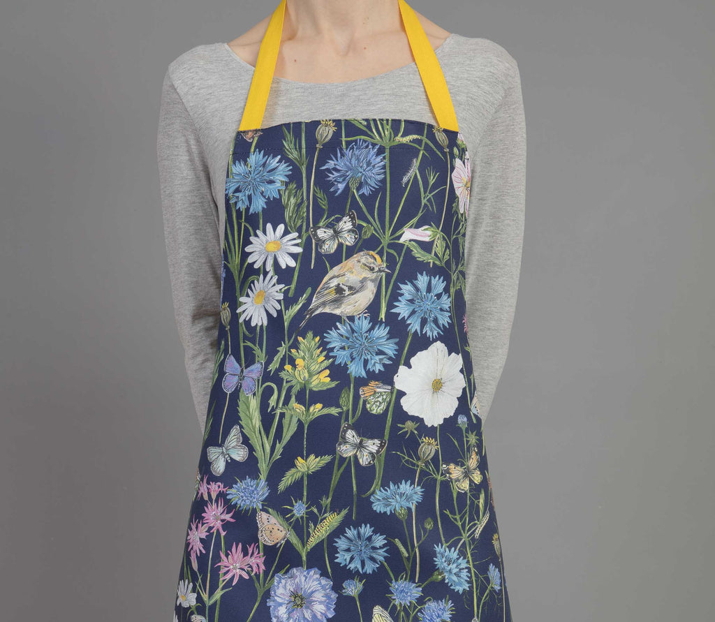 Bright and colourful bird and floral apron. Ideal for baking, a excellent gift for anyone that loves baking and nature, or lives in the countryside. Navy blue with yellow waist ties. Original apintings are used to create this pattern, including Goldcrests, 17 diffrent types of British Butterflies, Cornflowers, thistles, common mallow, cosmos and poppies.