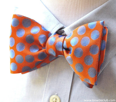 orange and blue woven polka dot bow tie on shirt