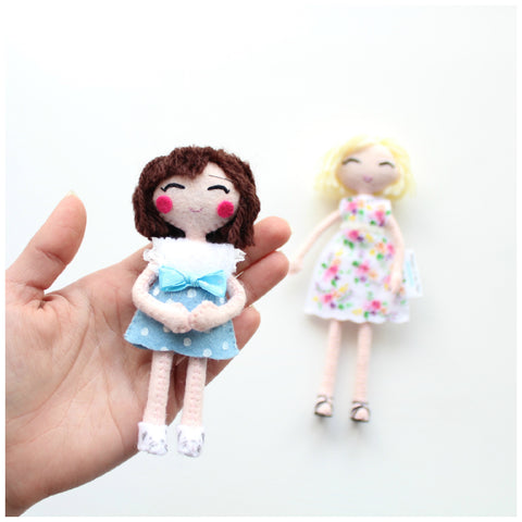 Little girl art doll. Rosy cheeks. Blue skirt and white top. Brunette doll.
