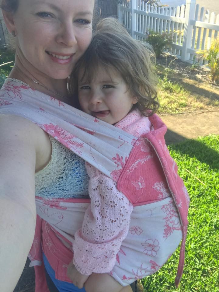 woman wearing toddler in pink gumnut baby meh dai carrier