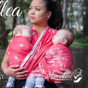 woman wearing twin babies in a coral and cream woven wrap
