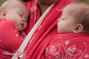 twin babies being worn in a coral and cream woven wrap