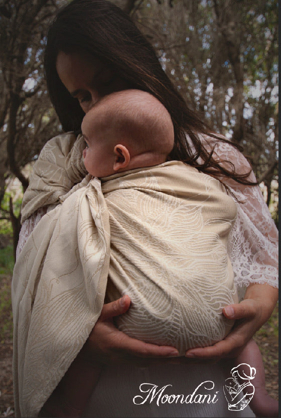 woman holding baby in a gold and cream ring sling carrier