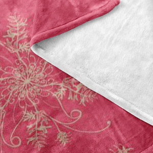 Coral and gold minky blanket with grevillea design showing white fleecy underside