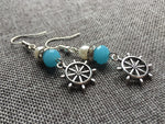 Silver charm earrings with boat rudder and blue and white resin ball