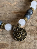 Bronze charm bracelet OM symbol and gray and white glass beads