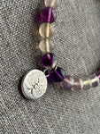Elastic bracelet with purple and transparent glass beads