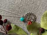 Silver charm necklace and turquoise glass ball