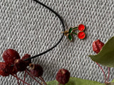Cherry charm necklace on black leather cord