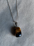 Silver charm necklace and tiger eye stone on a delicate silver chain