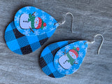 Snowman leather charm earrings on blue background