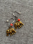 Gold elephant charm earrings on a silver hook and orange resin beads