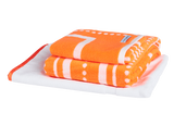 Vibrant orange and white luxury bath towel bundle with modern Art Deco pattern. Neatly folded Bath Towel, Hand Towels and Bath Mat made with 100% Turkish cotton.