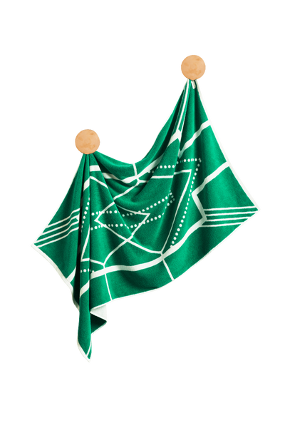 Designer Bath Towel in emerald green and white hanging on brass hooks. Turkish Bath Towel features modern Art Deco pattern and is made with 100% Turkish cotton.