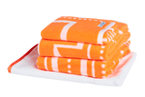 Vibrant Peach and white luxury bath towel set with modern Art Deco pattern. Neatly folded Bath Towels, Hand Towels and Bath Mat made with 100% Turkish cotton.