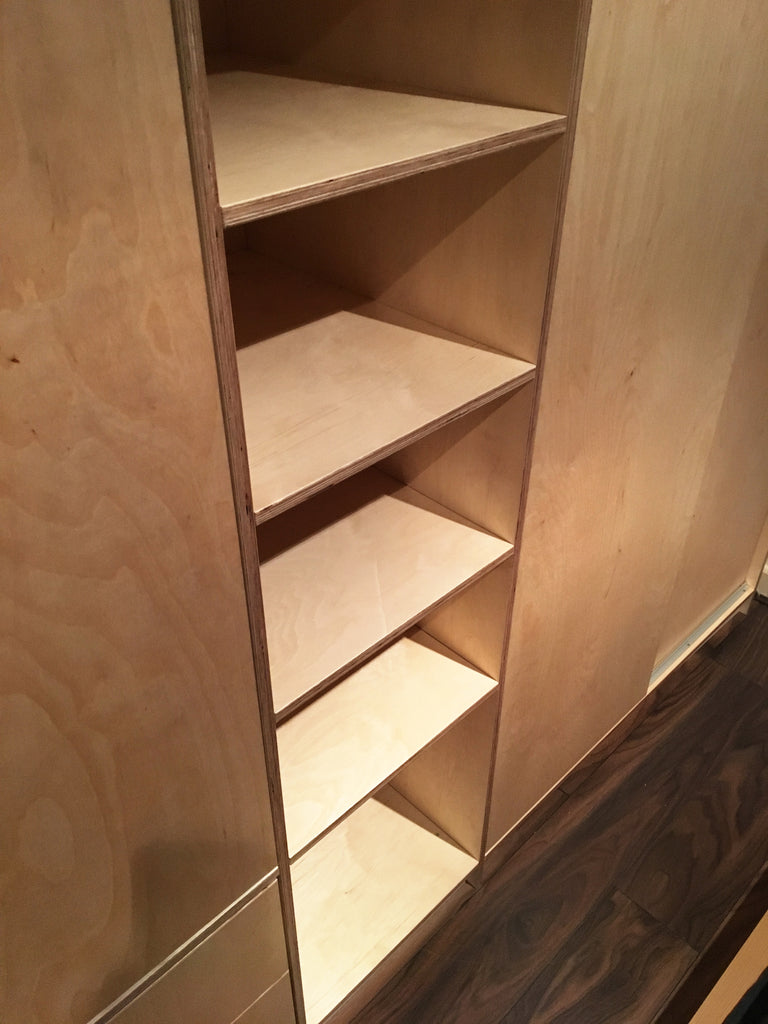 Bespoke plywood shelving unit as part of the wardrobe.